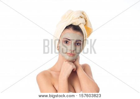 adorable girl takes care her skin with cleansing mask on face and towel on head isolated on white background. Health care concept. Body care concept. Young woman with healthy skin.