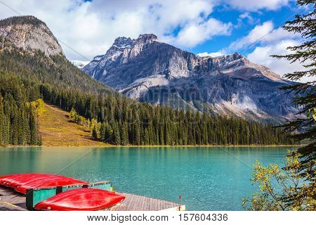 Shiny red kayaks are dried upside down. Emerald Lake in the Canadian Rockies. The concept of active tourism and vacation