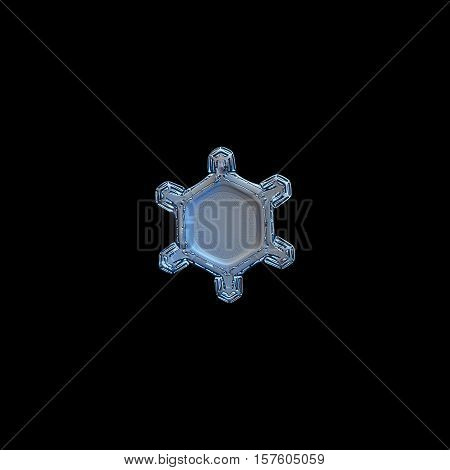 Snowflake isolated on white background: macro photo of real snow crystal, captured on glass surface with LED back light. This turtle-like snowflake contains unusual pattern of tiny dots around center.