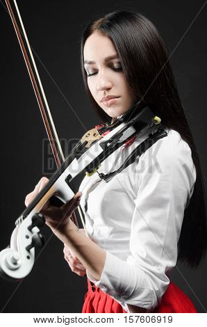 beautiful girl in the playing on violin black background
