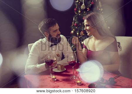 Beautiful young couple having a conversation on a romantic Christmas dinner drinking wine and eating cake