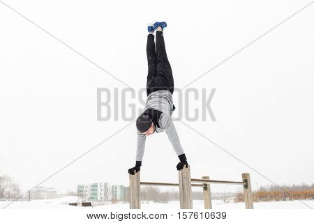 fitness, sport, training, people and exercising concept - young man on parallel bars doing handstand outdoors in winter