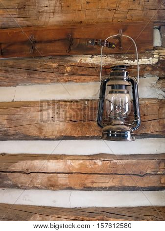 An old rustic lantern hangs on a wall in a log cabin