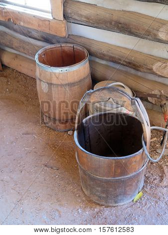 antique water or drinking barrels sitting next to a log cabin