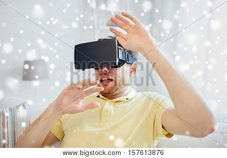 technology, augmented reality, gaming, entertainment and people concept - scared young man with virtual headset or 3d glasses playing game over snow