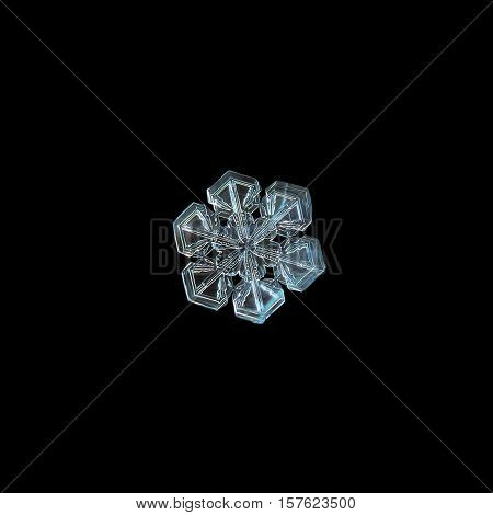 Snowflake isolated on black background. This is macro photo of real snow crystal with short broad arms and almost perfect symmetry.