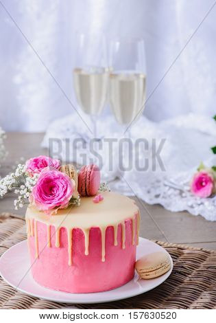 Homemade wedding cake closeup, decorated with raspberry and cream French macarons