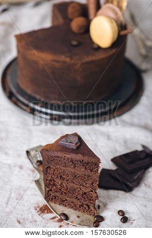 Slice of a dark chocolate cake closeup on a vintage silver cake server