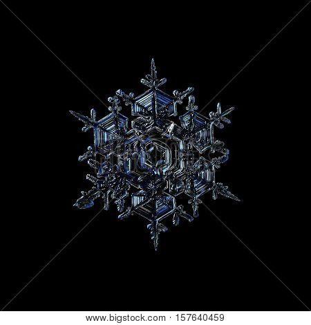 Real snowflake photo on glass with back light, isolated on black background.
