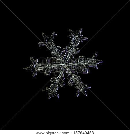 Snowflake isolated on black background. This is macro photo of real snow crystal: stellar dendrite with traditional shape and six ornate arms with many small details.