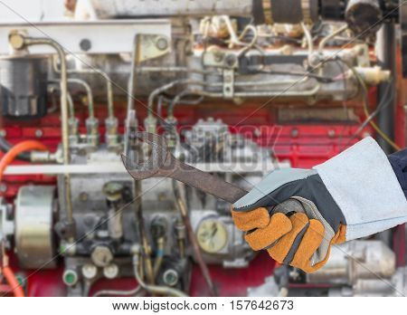 Hand In Glove Holding Spanner With Engine
