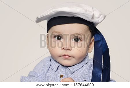 Portrait of a cute baby boy looking at camera wearing a sailor hat.    Adorable child with a nautical hat.