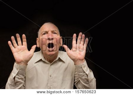 The old man with a emotions on a dark background