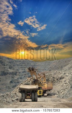 Heavy mining dump trucks are being loaded with iron ore on the opencast mining on sunset