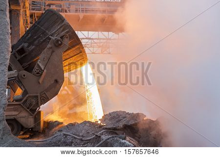 Heavy industry. Part of the process in metallurgy. Pouring the hot melt from the vat.