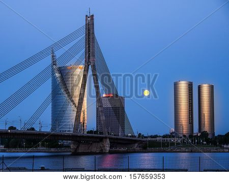Riga Latvia - May 21 2016: Night view on cable-braced bridge over Daugava river and new buildings on over bank of it.
