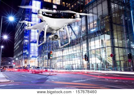 Close up of hovering drone taking pictures of city of London at night