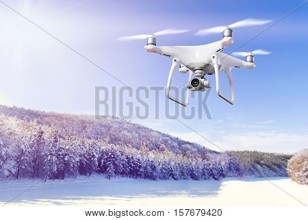 Hovering drone taking pictures of snowy white meadow and forest and clear blue sky