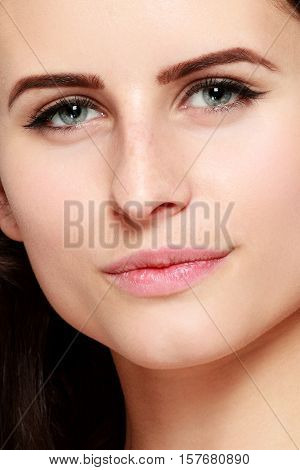 Beautiful woman face close up portrait young studio on gray. emotions concept. girl in the camera. portrait. Natural soft make up. Beauty Woman face Portrait. Beautiful Spa model Girl