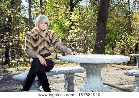The girl sits at the table. She strolls in the autumn park.