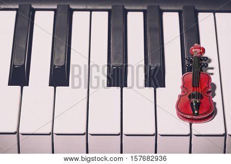 Music concept. Red decorative violin on the piano.