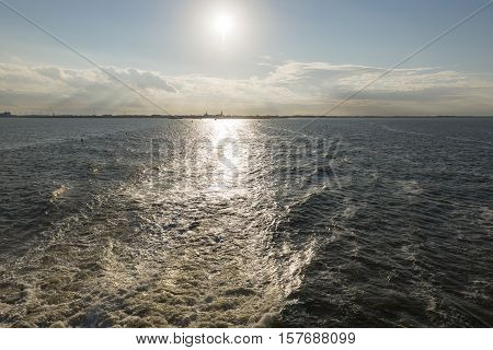 Wake behind the ferry from the Mainland to Vlieland with on the horizon the town of Harlingen in the Netherlands