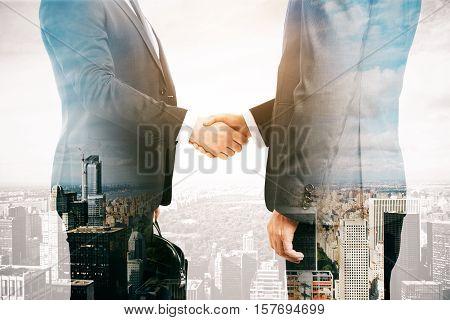 Businessmen shaking hands on city background. Double exposure. Partnership concept