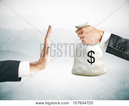 Hand saying no to money bag on abstract background. Stop corruption concept