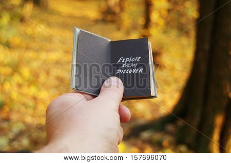 Hand holding a book with text Dream Travel Discover