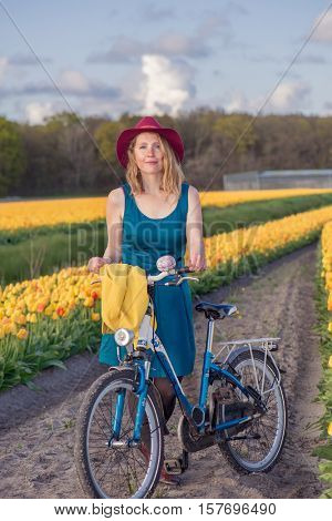 Smiling tourist in a dress and hat on standing with her bike in a yellow tulips field