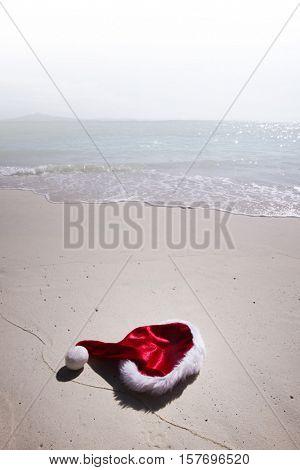 Closeup christmas hat on a white stropical sandy sea beach