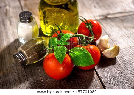 Olive oil tomato and herbs on rustic wooden table
