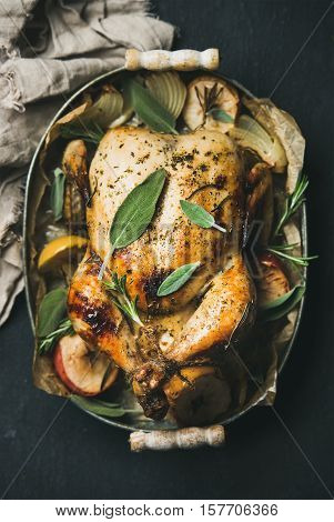 Oven roasted whole chicken with onion, apples and sage in serving tray over dark stone background, top view, selective focus, vertical composition. Celebration food concept