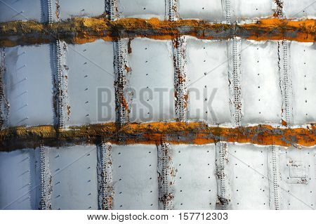 Background image shows closeup of a steel tank. Closeup shows welds seams and rivets.