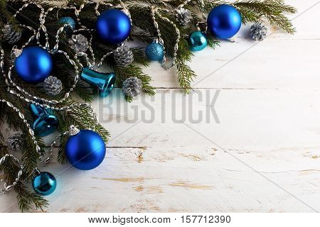 Christmas background with silver pinecone and blue ornaments. Christmas party decoration with shiny balls. Copy space.