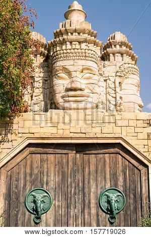 Stone faces of a temple and wooden portal with door knocker shaped like elephant's head.