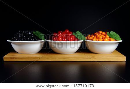 sea buckthorn,currant,choke berry,blackberry with green leaves on a black background