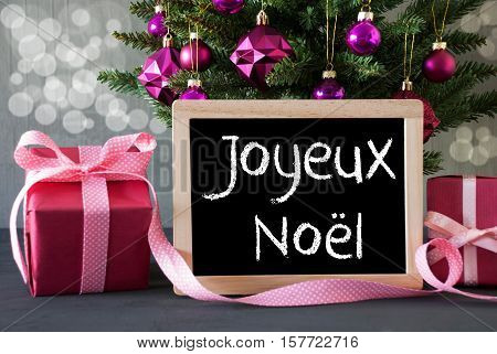 Chalkboard With French Text Joyeux Noel Means Merry Christmas. Christmas Tree With Rose Quartz Balls And Bokeh Effect. Gifts Or Presents In The Front Of Cement Background.