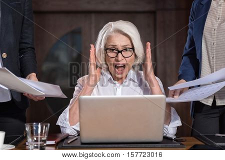 Time to panic. Angry tired elderly boss shouting while working on a laptop in office and feeling tired.