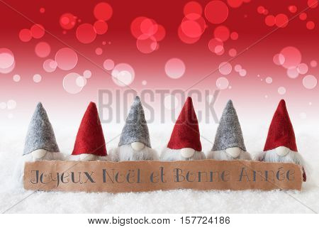 Label With French Text Joyeux Noel Et Bonne Annee Means Merry Christmas And Happy New Year. Christmas Greeting Card With Red Gnomes. Bokeh And Christmassy Background With Snow.