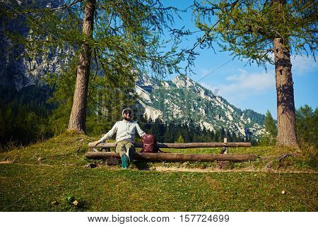 Wide low angle shot of the bearded man who is sitting on the bench fully relaxed and admiring the vista of the mountain