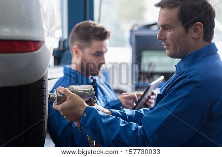 Smart tool. Positive adult professional car mechanic changing wheel while using pneumatic wrench while reparing car in auto service center