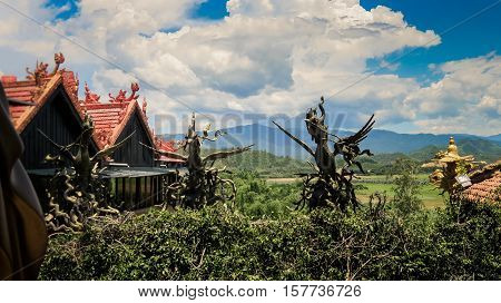 Small Pagoda Buildings Among Plants Against Hills Blue Sky