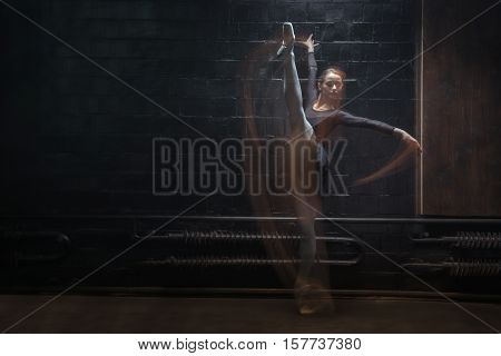 Amazing flexibility. Involved concentrated young gymnast showing the twine while raising her hands and being in motion