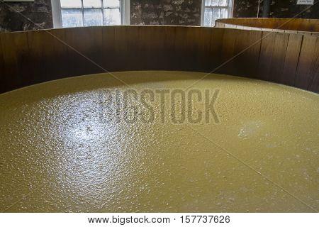 Mash in oak barrel fermentation tanks inside stone distillery.