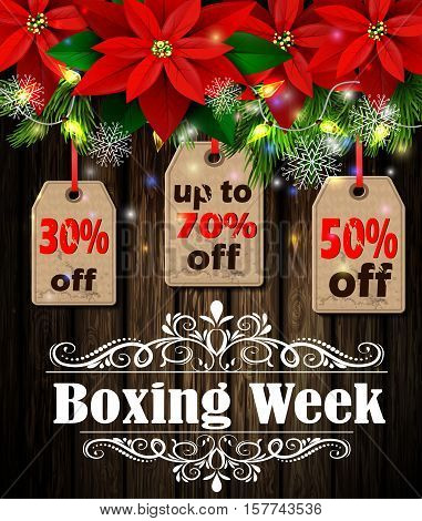 Boxing week sale tag with evergreen trees with poinsettia christmas lights isolated on wooden wall