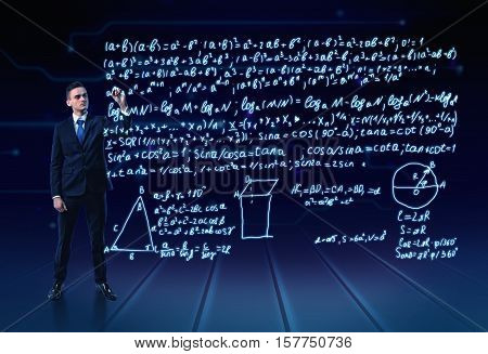 A man in a suit full-height writing a lot of trigonometrical formulas in the air. Education. Geometrical calculating. Formulas and equations.