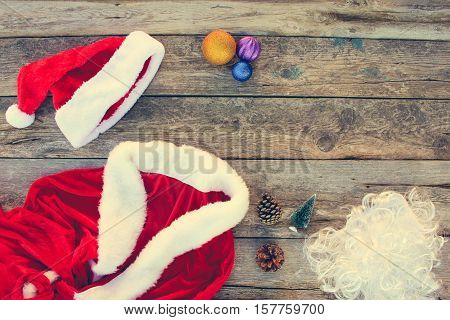 Santa Claus suit, small tree, pinecone, Christmas balls on wooden background. Top view. Toned image.