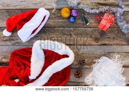 Santa Claus suit, small tree, pinecone, Christmas balls on wooden background. Top view.