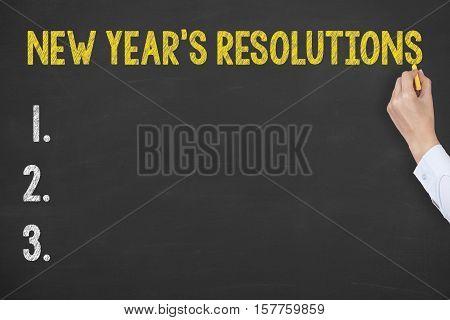 Human Hand Writing New Year's Resolutions on Blackboard